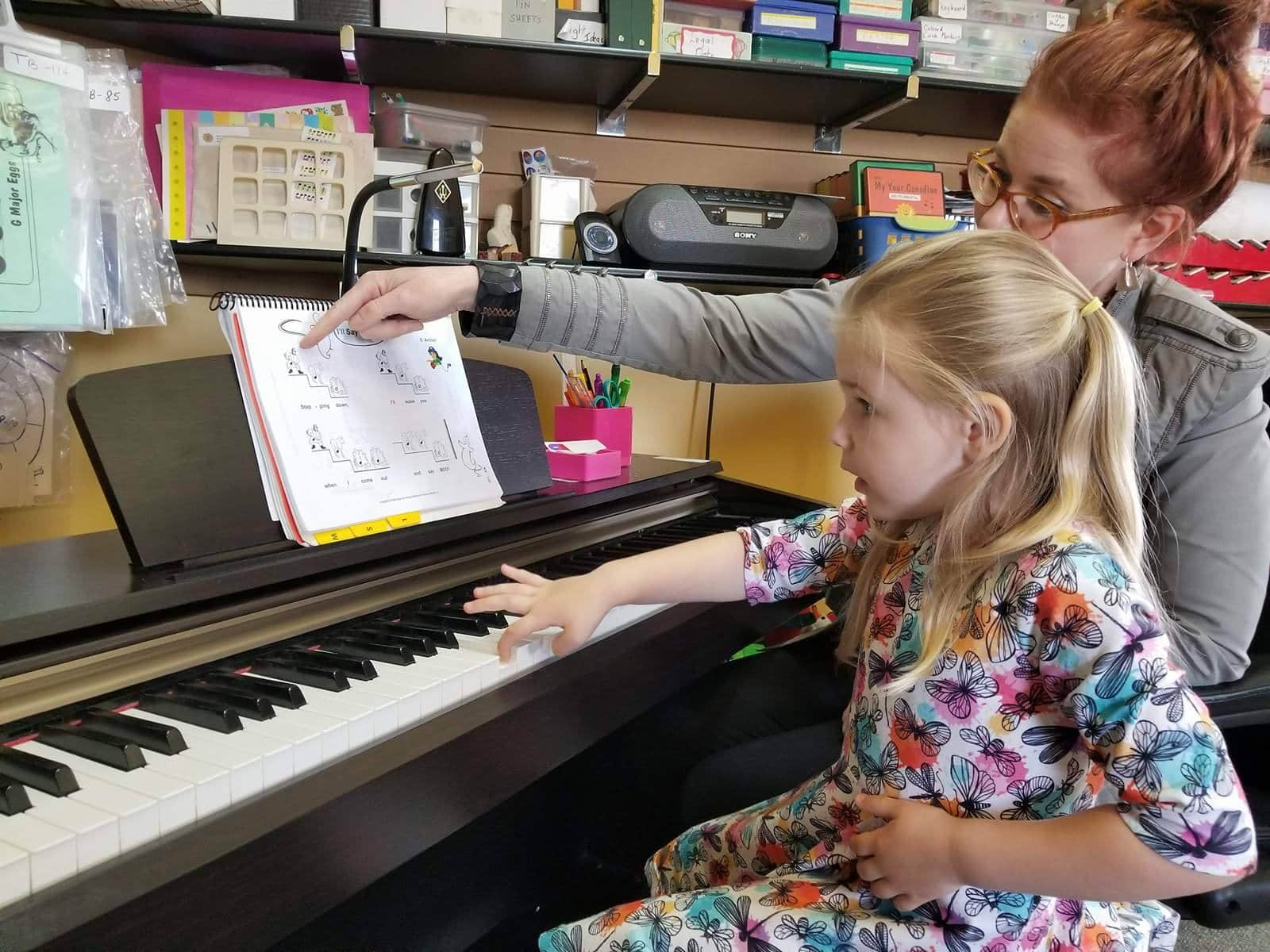 Jennifer Allan helping an MYC student play the piano